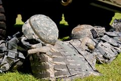 Combat gear. Camouflage combat flak jackets and helmets lined up on the ground Royalty Free Stock Images