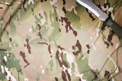 Combat knife on military camouflage fabric background Royalty Free Stock Photography