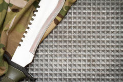Combat knife on military camouflage fabric and metal background Stock Images