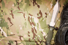 Combat knife and shoes on military camouflage fabric background Stock Photo
