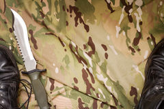 Combat knife and shoes on military camouflage fabric background Stock Photos