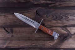 Combat knife on wooden table. Combat knife on wooden background. Bayonet for Kalashnikov rifle Stock Photography