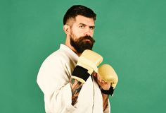 Combat master practices attack or defense posture. Man with beard in white kimono on green background. Japanese martial arts concept. Karate man with serious stock images