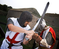Combat of two knights. In tower background Royalty Free Stock Photo