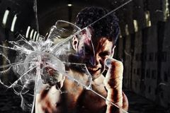 Combatiente apto que perfora una pared de cristal Fotografía de archivo libre de regalías