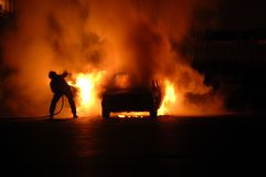 Combatiente de fuego en resplandor del coche Foto de archivo libre de regalías