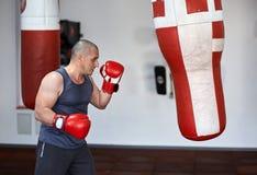 Combatiente de Kickbox que trabaja en punchbags Foto de archivo libre de regalías