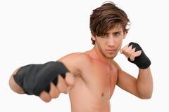 Combatiente de los artes marciales que ataca con su puño Fotografía de archivo libre de regalías