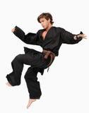 Combatiente de los artes marciales que realiza un retroceso del salto imagenes de archivo