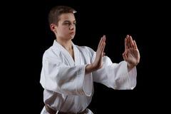 Combatiente del karate en el kimono blanco aislado en negro Fotografía de archivo libre de regalías