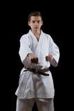 Combatiente del karate en el kimono blanco aislado en negro Imágenes de archivo libres de regalías