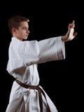 Combatiente del karate en el kimono blanco aislado en negro Imagen de archivo