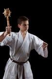 Combatiente del karate en el kimono blanco aislado en negro Fotografía de archivo