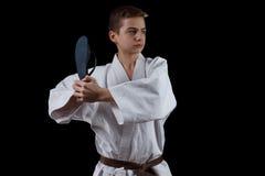 Combatiente del karate en el kimono blanco aislado en negro Imagen de archivo libre de regalías