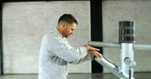Combatiente del kung-fu que practica artes marciales con el maniquí de madera 4k almacen de metraje de vídeo