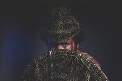 Combatiente del mago con el escudo y el casco del oro y de sh geométrico Foto de archivo