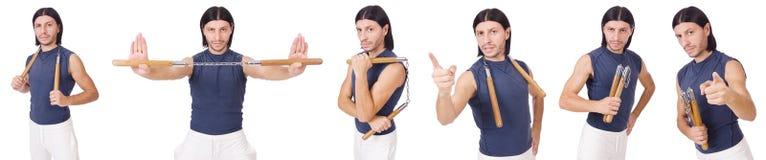 Combatiente divertido del karate con los nunchucks en blanco Foto de archivo
