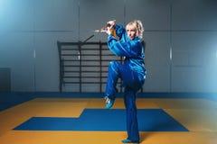 Combatiente femenino del wushu con la espada en la acción Imagen de archivo libre de regalías