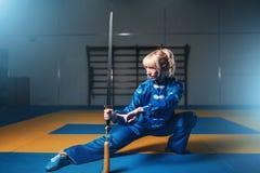 Combatiente femenino del wushu con la espada en la acción Foto de archivo libre de regalías