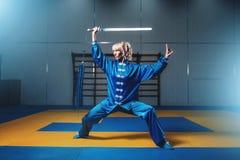 Combatiente femenino del wushu con la espada en la acción Imagen de archivo
