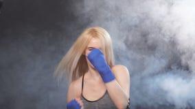 Combatiente femenino kickboxing atractivo joven con los sacadores practicantes del pelo rubio, cámara lenta almacen de metraje de vídeo