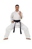 Combatiente femenino que realiza postura del karate Foto de archivo