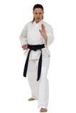 Combatiente femenino que realiza postura del karate Imagenes de archivo