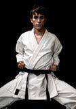 Combatiente masculino joven del karate del alto contraste en negro fotografía de archivo