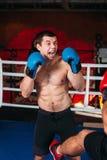 Combatiente muscular con una cara enojada en un anillo imagenes de archivo