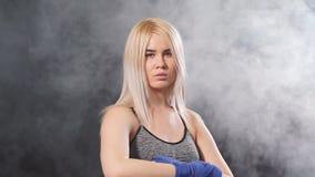 Combatiente tailandés femenino rubio joven de Muay que envuelve sus manos con el vendaje elástico azul C?mara lenta almacen de video