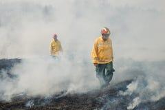 Combatientes de fuego que cruzan el terreno socarrado Imagen de archivo libre de regalías