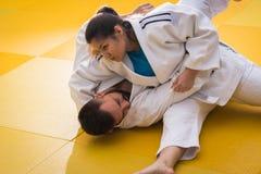 Combatientes del judo de la mujer y del hombre en pasillo de deporte Imagenes de archivo