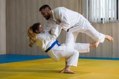 Combatientes del judo de la mujer y del hombre en pasillo de deporte Foto de archivo