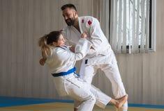 Combatientes del judo de la mujer y del hombre en pasillo de deporte Imagen de archivo libre de regalías