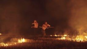 Combatientes libres que baten con las antorchas en los fuegos de la noche en campo 4K metrajes