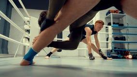 Combatientes que hacen estirando las piernas antes del entrenamiento de encajonamiento en el anillo de la caja en club de la luch metrajes
