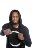 Combative African man making a fist. Combative African man in a black hood making a fist in a threatening gesture as he looks at the camera with a mean Royalty Free Stock Photos