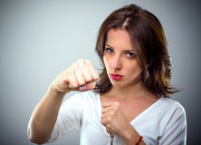 Combative young woman punching at the camera Royalty Free Stock Photography