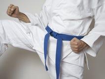 Combattant avec le coup-de-pied bleu d'arts martiaux de ceinture Photo stock