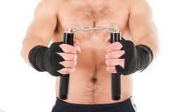 Combattant d'arts martiaux tenant les nunchucks noirs avec Photographie stock