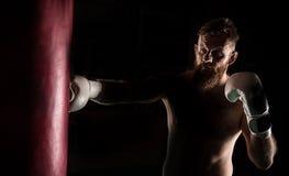 Combattant musculaire de hippie donnant un coup-de-pied puissant pendant une pratique avec un sac de boxe Images stock
