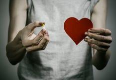 Combatte contro le droghe e l'argomento di tossicodipendenza: dedichi la tenuta delle pillole narcotiche su un fondo scuro fotografia stock libera da diritti