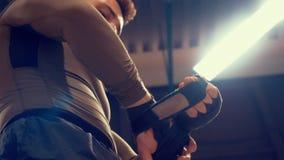 Combattente dell'uomo che avvolge le mani con la fasciatura di pugilato prima dell'addestramento d'inscatolamento nel club di lot archivi video