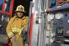 Combattente di fuoco che si siede alla porta dei vigili del fuoco Fotografia Stock Libera da Diritti