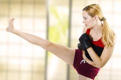 Combattente femminile che dà dei calci all'alto lato del piedino. Forma fisica Fotografia Stock