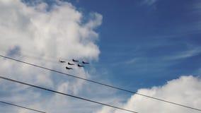 Combattenti moderni del gruppo militare in volo nel parallelo del cielo ai cavi ad alta tensione stock footage