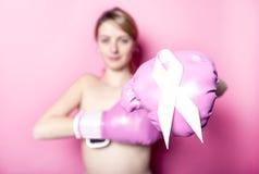 Combatti per la donna del cancro al seno con il simbolo su fondo rosa immagini stock