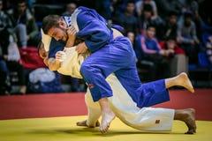 Combatti sul tatami due judoists maschii degli atleti nel finale in fan del fondo Fotografie Stock