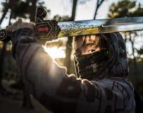 Combattimento del ragazzo del guerriero sulla montagna al tramonto immagine stock libera da diritti