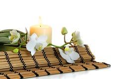 Combinación con las flores de la orquídea, vela aromática ardiendo del balneario y Imagen de archivo